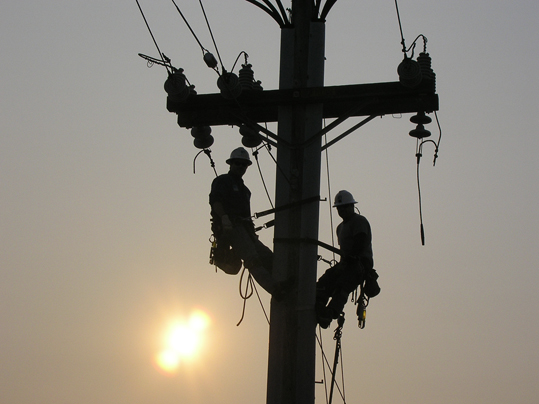 Eugene McCandless caught a silhouette of two linemen in the day's waning light.