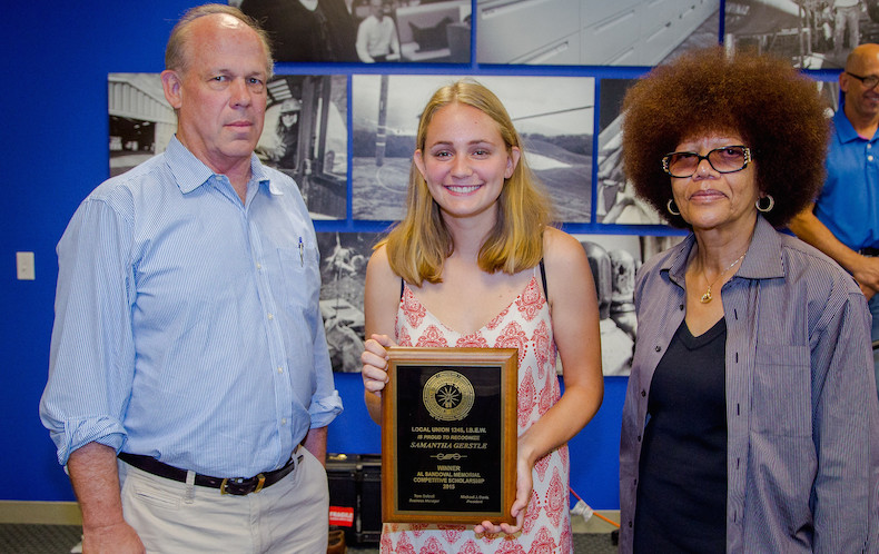 Samantha Gerstle accepts plaque from Business Manager Tom Dalzell, left, and retired Senior Assistant Business Manager Dorothy Fortier, right, who served as contest judge.