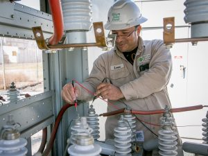 Leon Alcantar checks capacitors at the substation
