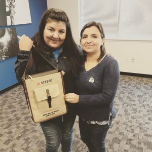 """Organizing Steward Nilda Garcia (left) gave Carla Silva her pin of Rosie the Riveter which states """"A Woman's Place is In Her Union!""""  In exchange, Carla gifted Nilda her satchel with the STESEC insignia embroidered on the flap."""