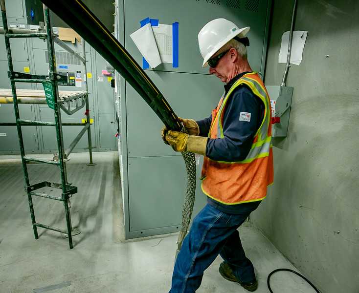 Mike McCarthy pulls cable into a new apartment building.