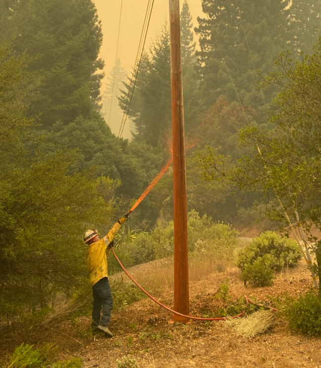 A SIPT crew member sprays a pole with fire retardant in the CZU fire zone. Photo by Trevor Dirksen